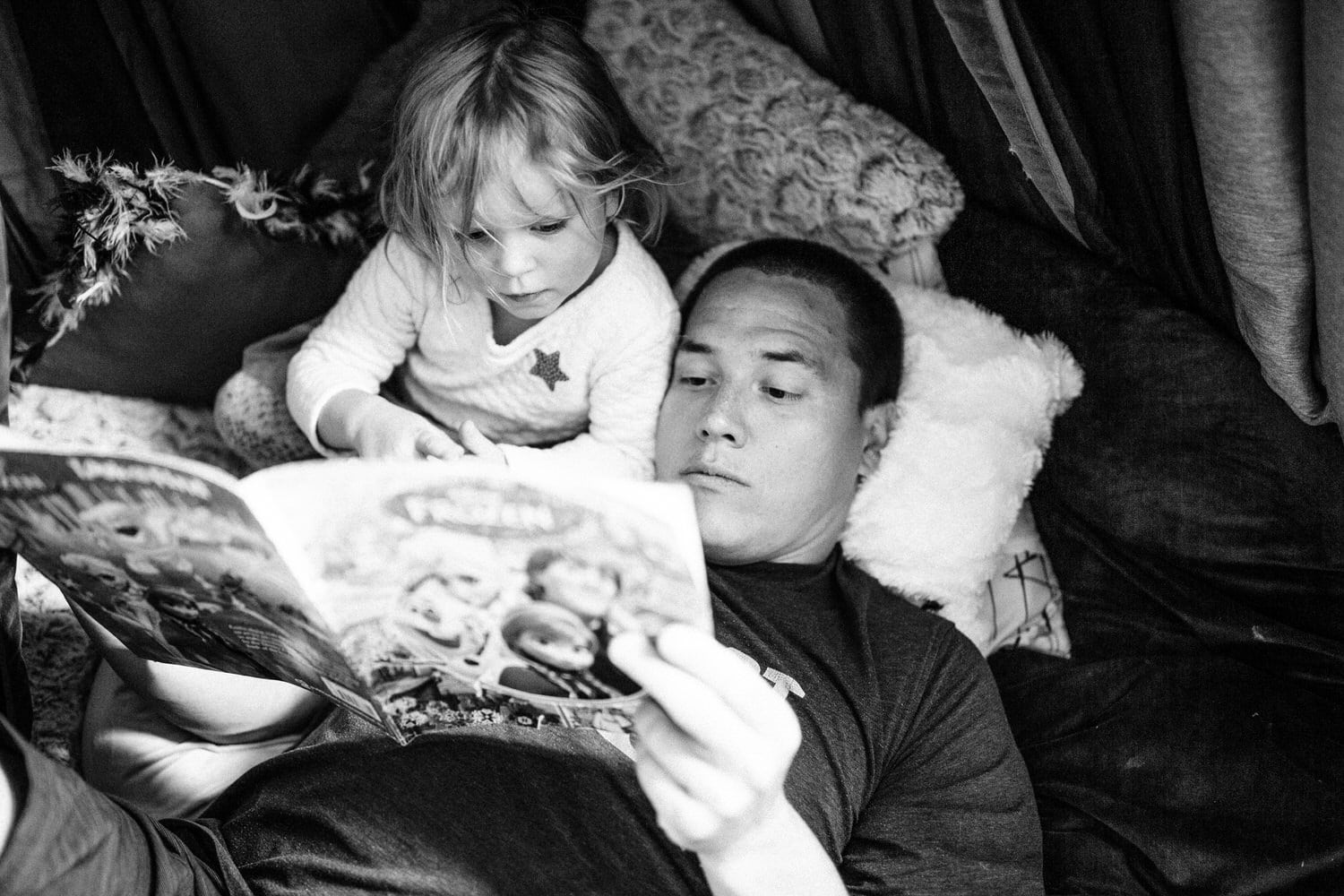 Toddler and daddy reading a book in the toddlers room located in Calgary Alberta