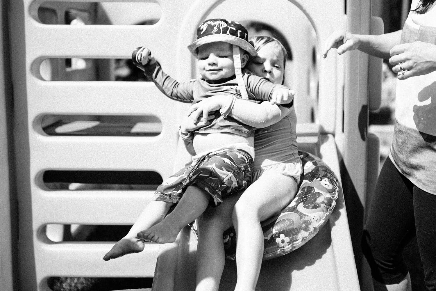 a photograph of two children sliding down a water slide during a warm summer day in Calgary