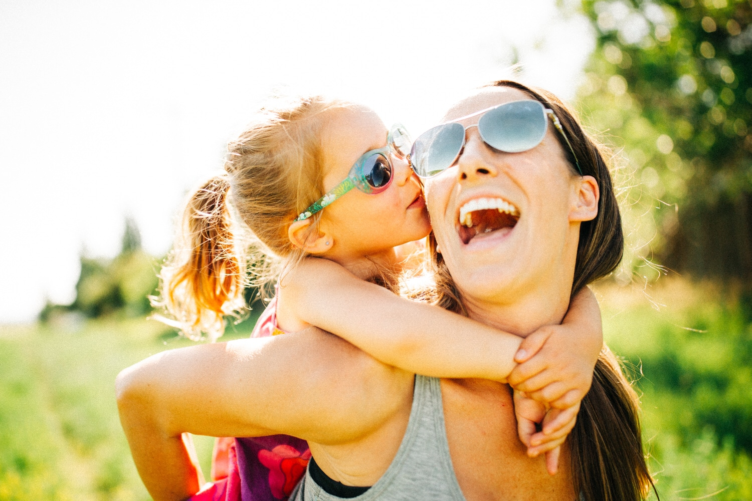 a young girl laughing and kissing her moms face during a family photography shoot in Calgary