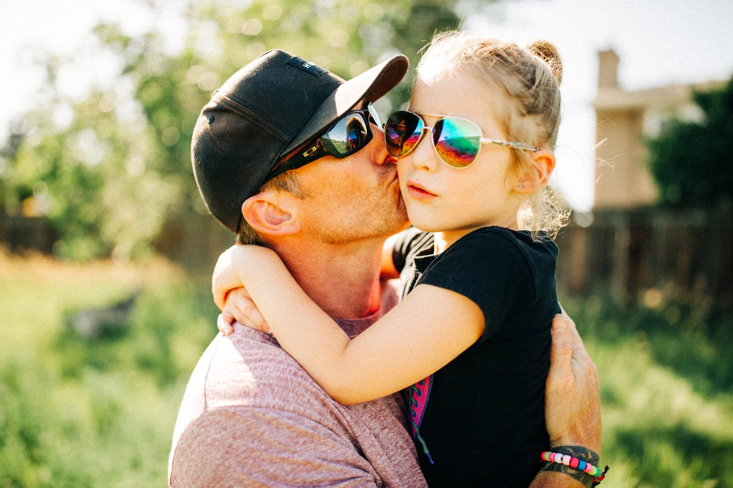 a dad hugging her daughter in a park late afternoon during their family portrait shoot