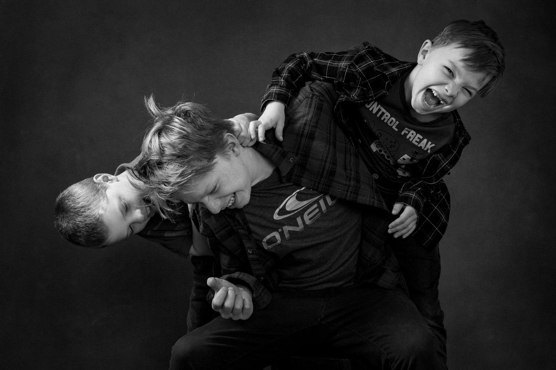 Three boys having fun during an unposed photography studio shoot