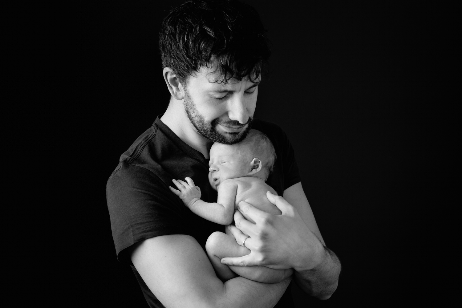 a newborn baby held by his Dad during a studio photography shoot