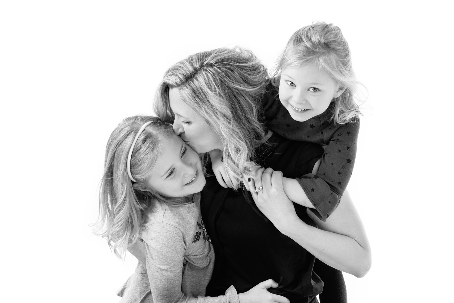 Mom and two daughers laughing inside OKES Portraits studio
