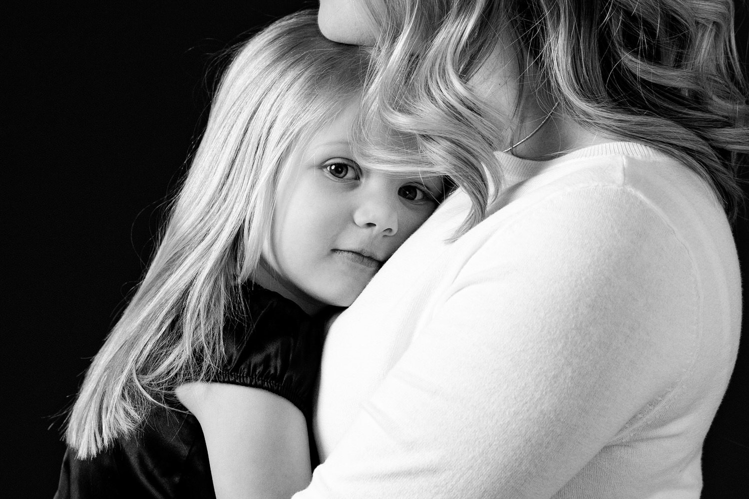 a young girl held by her mom photographed in Calgary's best portrait studio