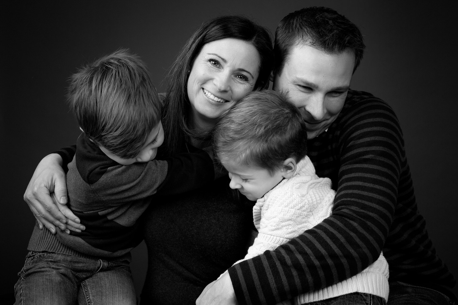 family smiling and loving their connection during a Calgary portrait studio shoot