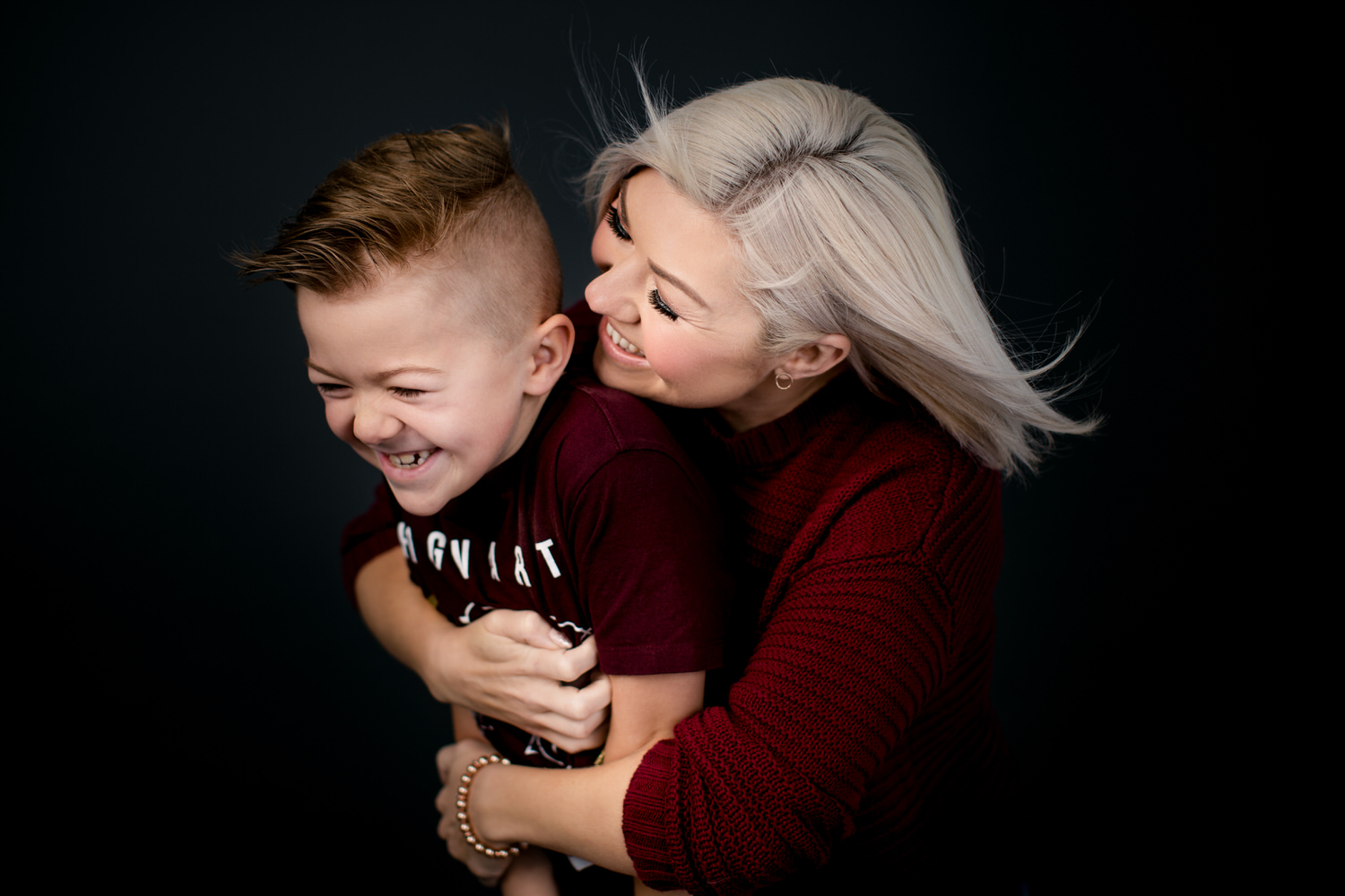A mother hugging her son at OKES Portraits studio in Calgary