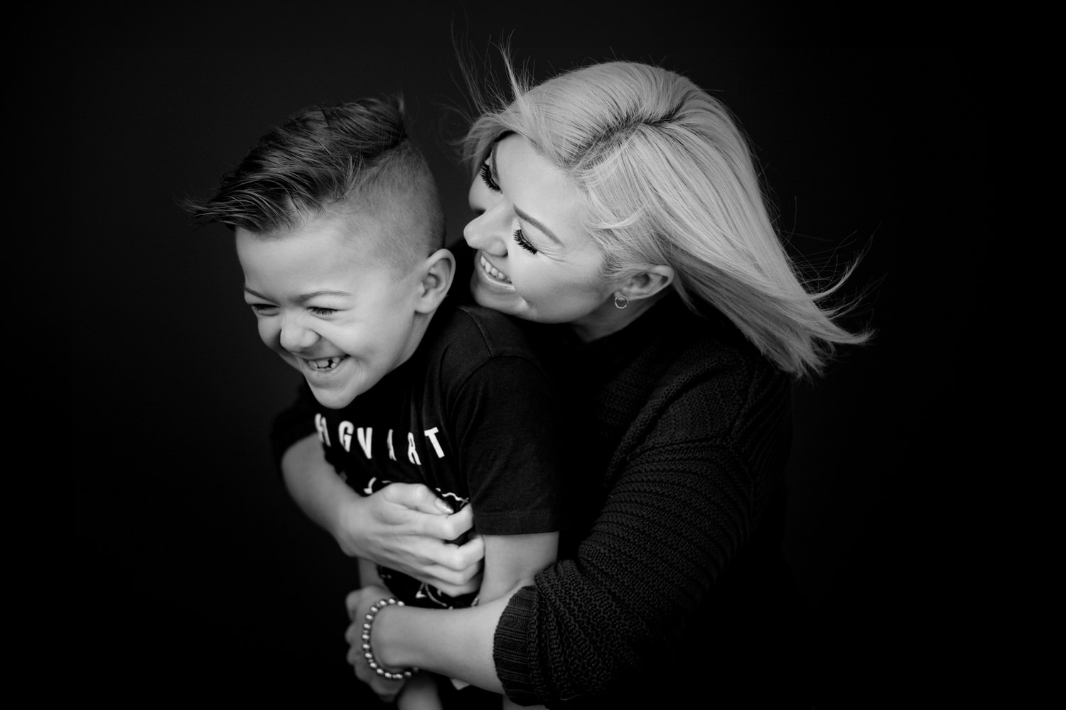 Mom hugging and tickling her son in OKES Portraits Studio in Calgary
