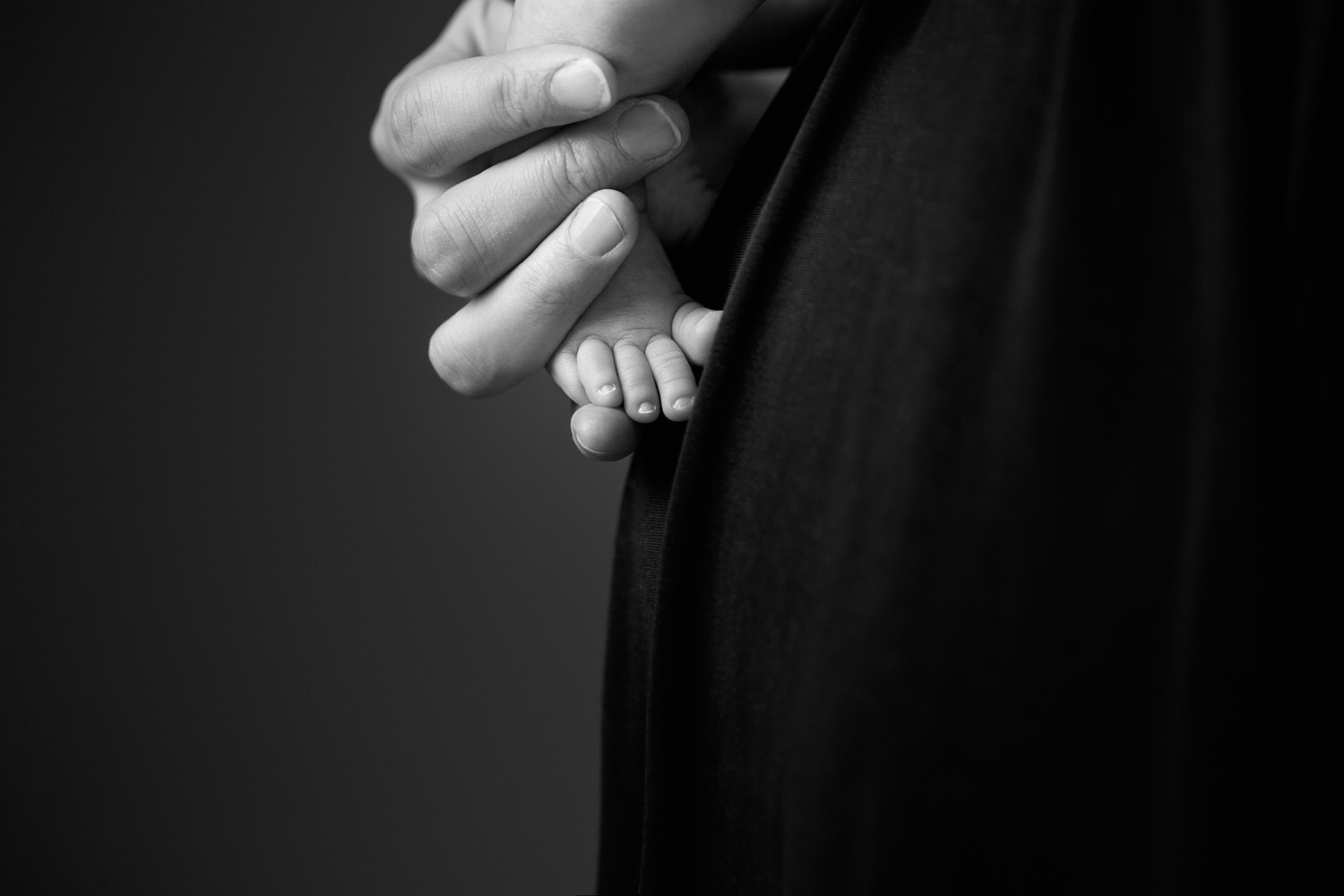 mom is holding her baby's little toes during an indoor studio photography shoot