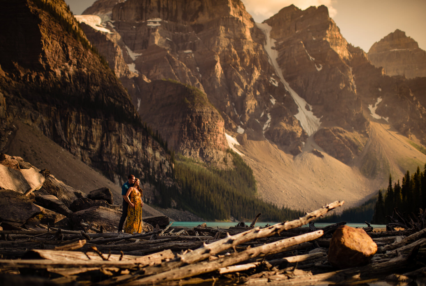 A couple holding each other as the sun goes down at Moraine Lake