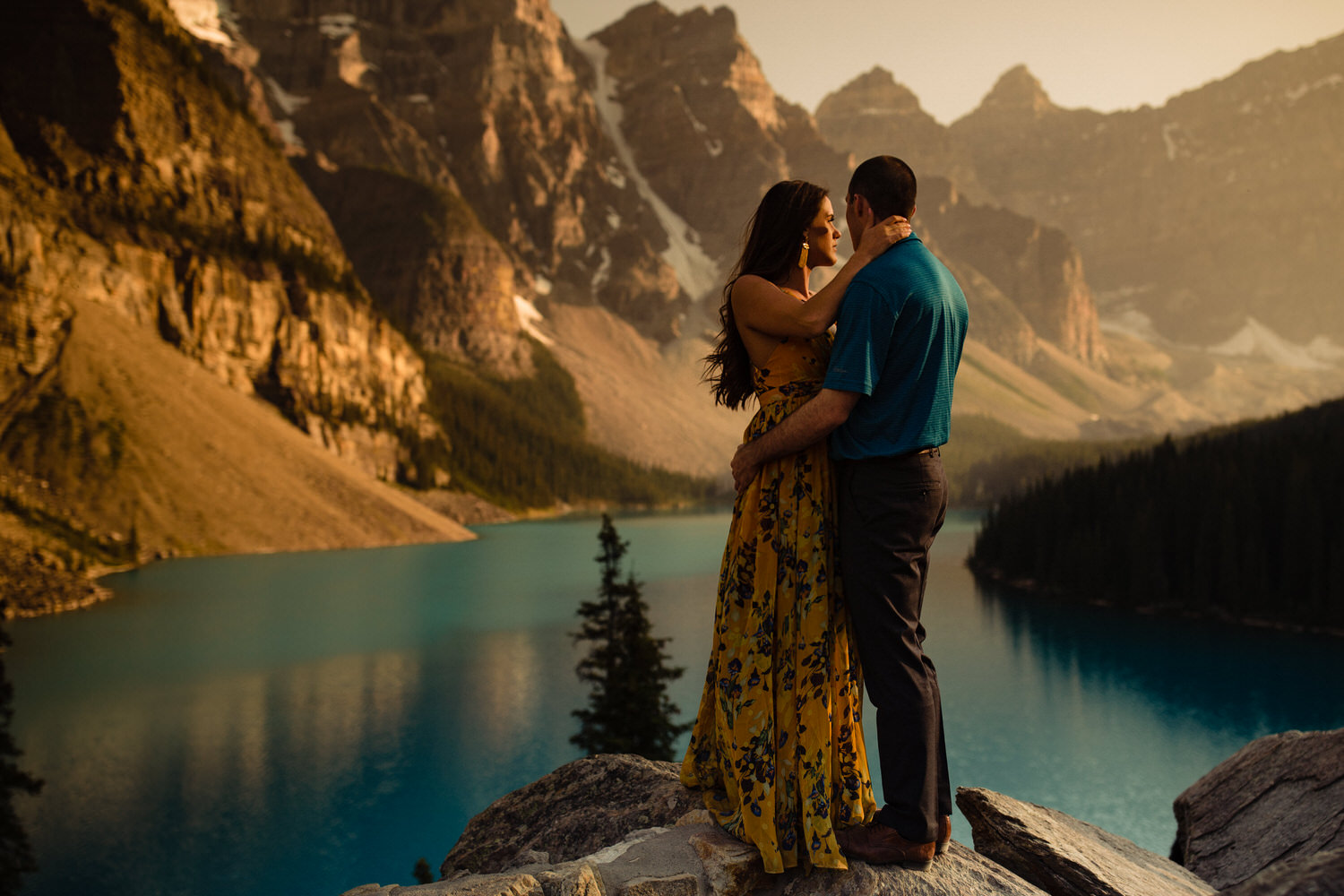 Engagement photo at Moraine Lake with couple holding each other as the sun goes down