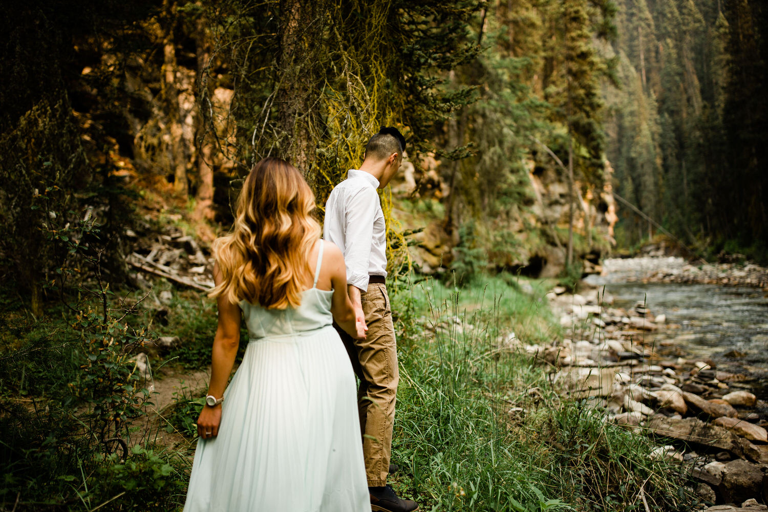 A newly engaged couple walking together along Johnston Canyon's flowing water