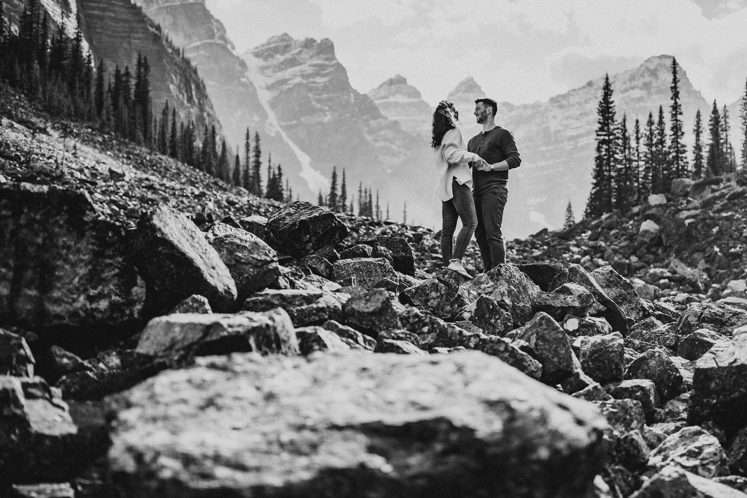 A couple laughing with big mountains in the background at Moraine Lake