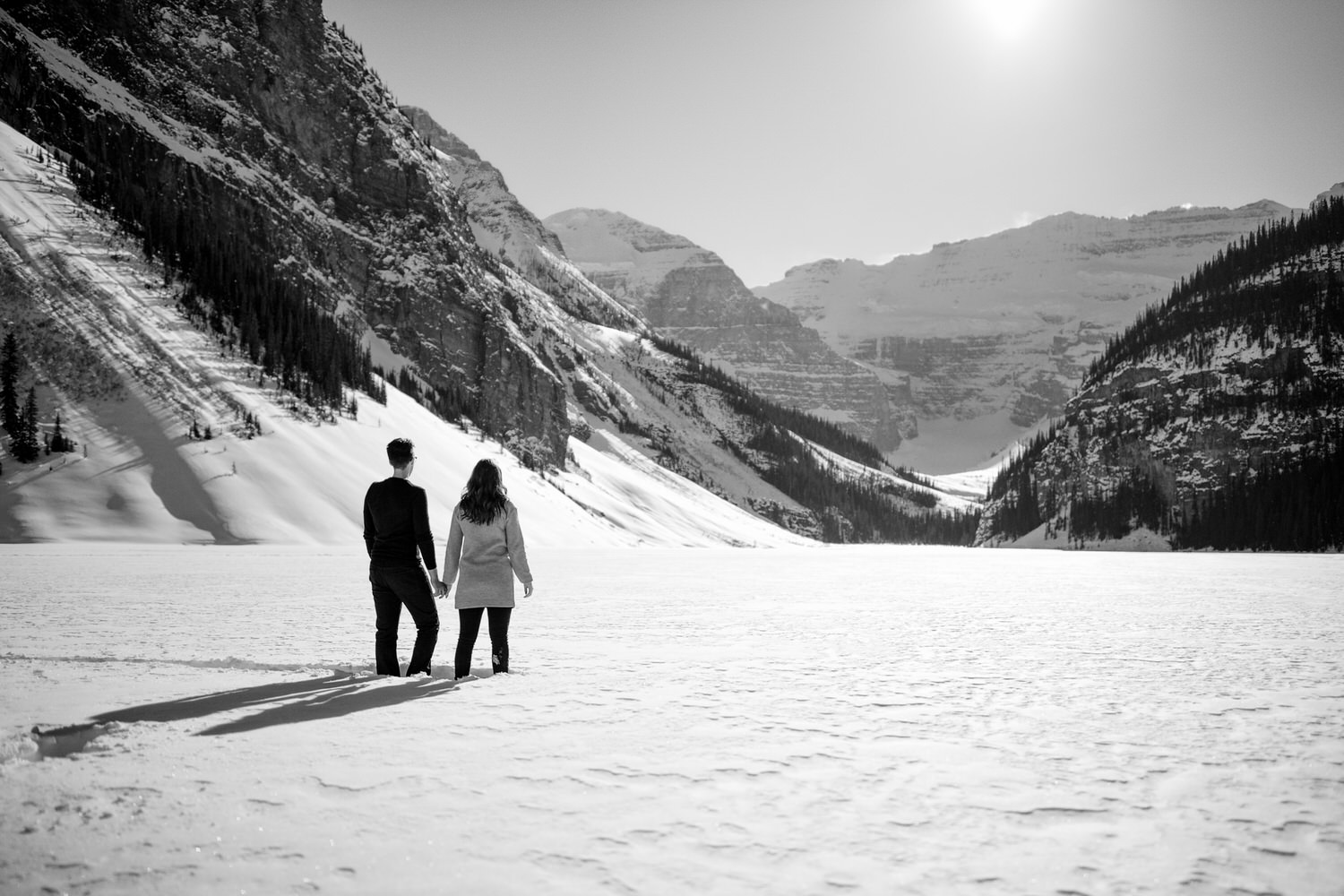 A couple looking out to Victoria Glacier holding hand at Lake Louise
