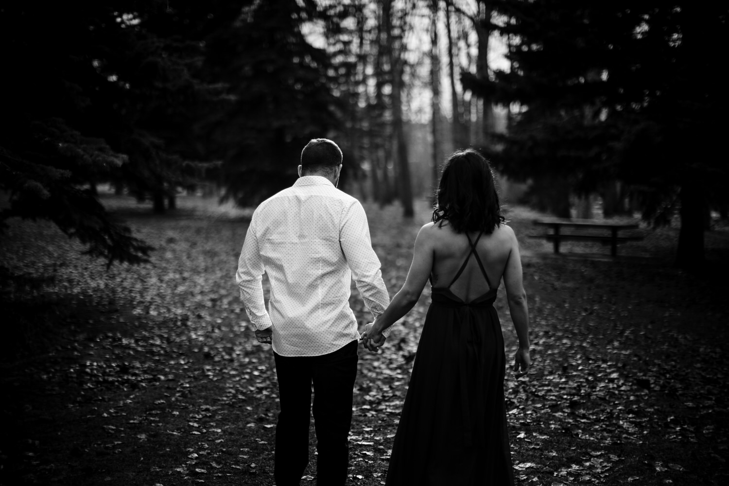 A photograph of a couple walking in Calgary park during their engagement shoot