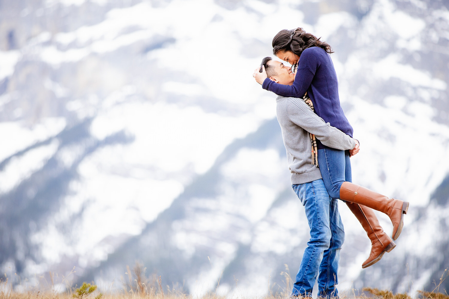 A lady jumping up into her partners arm during an engagement shoot in Banff National Park