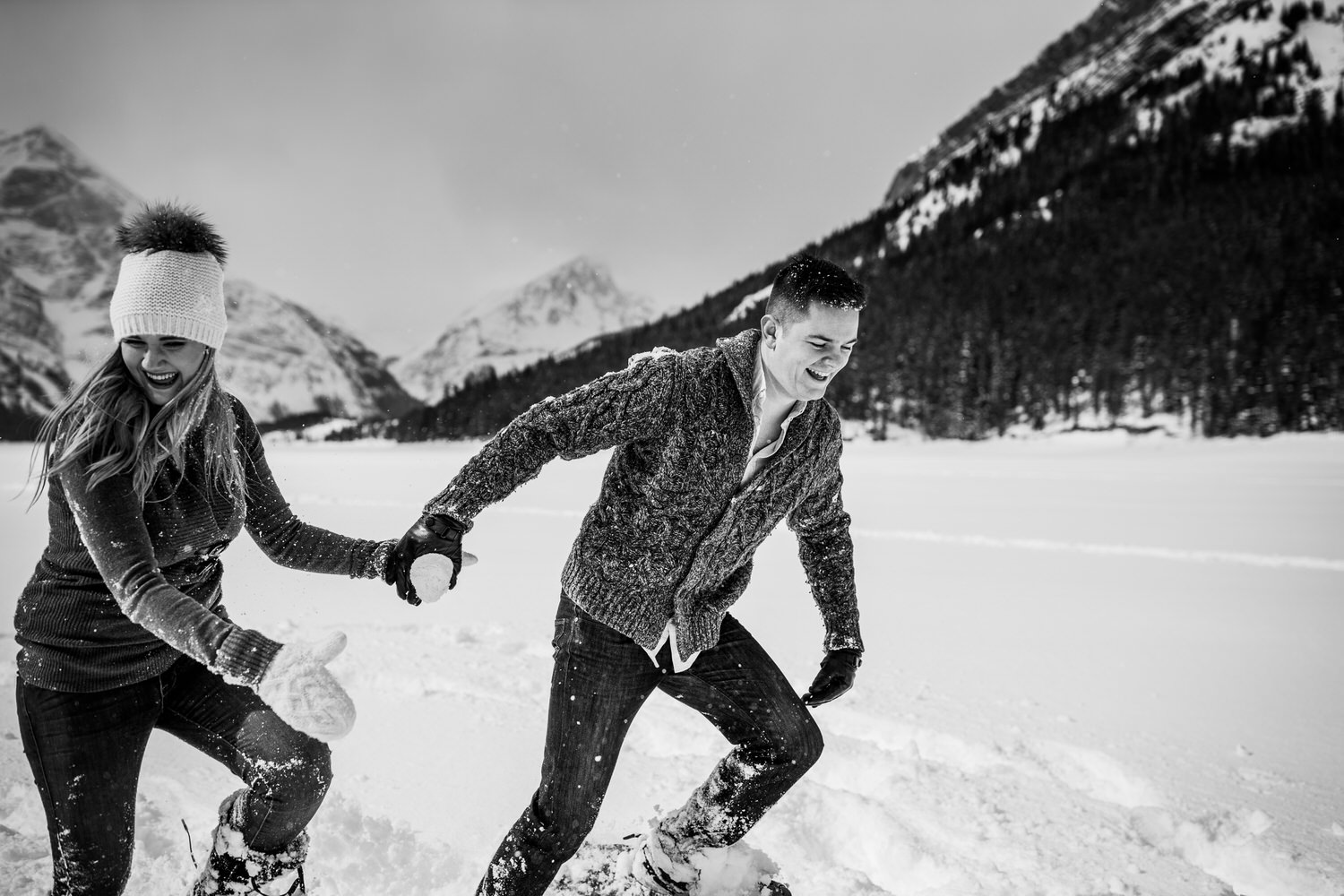 A couple running in Kananaskis Country in the winter with snowshoes on.