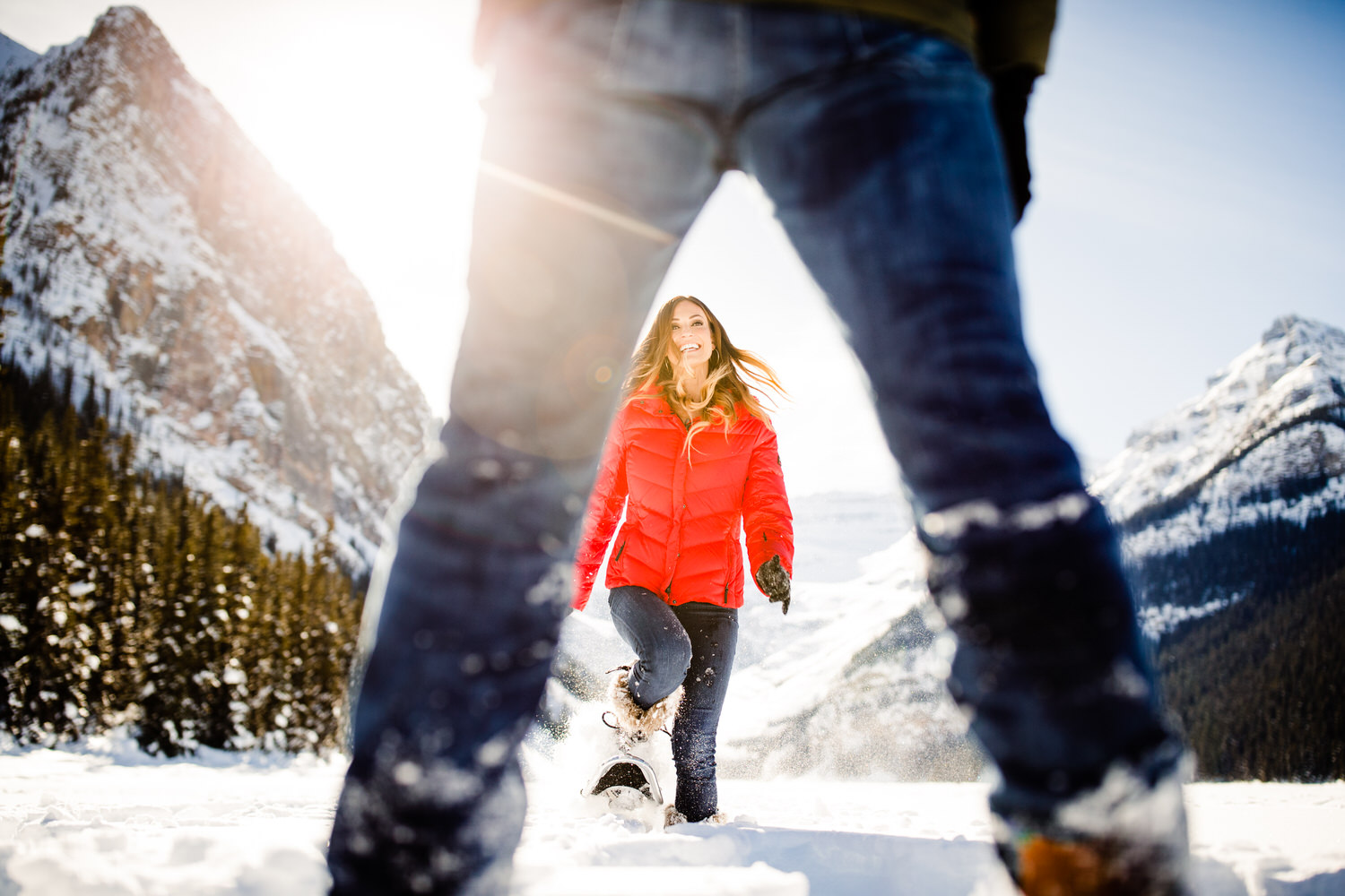 A lady in red running with snowshoes on towards her fiancé on a frozen Lake Louise.