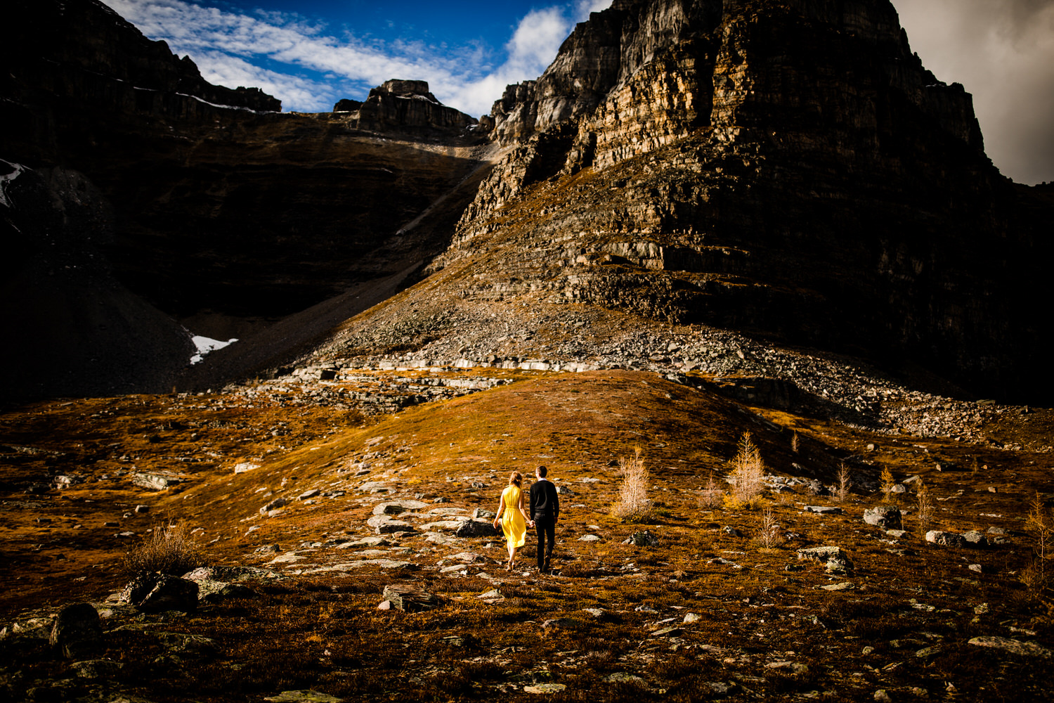 A photograph of a couple walking within the valley of the ten peaks Banff National Park