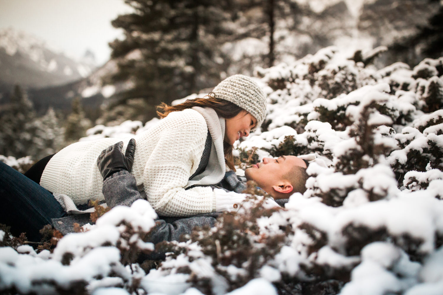 A couple laying down in the snow during a winter day in Banff National Park