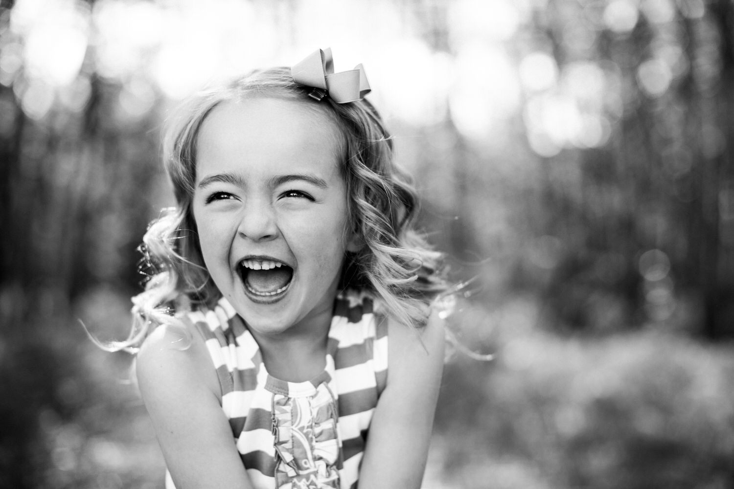 a girl laughing during a Calgary portrait photography shoot in the park