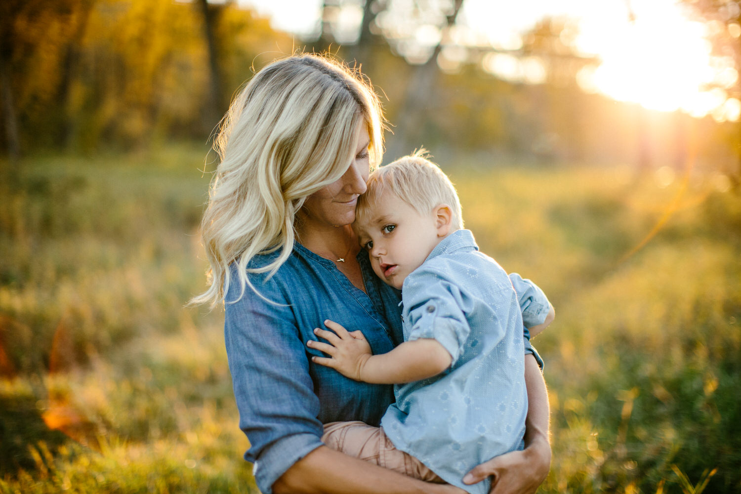 evening sunset photoshoot in Calgary Fish Creek park with a boy in the moms arms