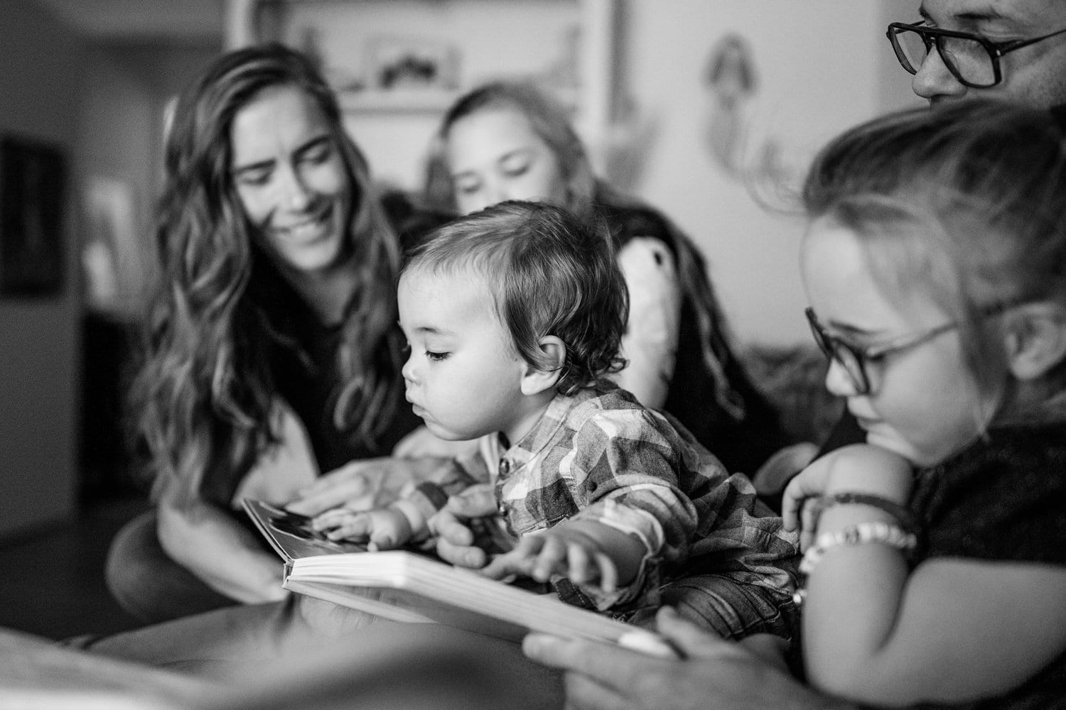 A toddler is reading a book on a bed in Calgary as the whole family laugh and play around him