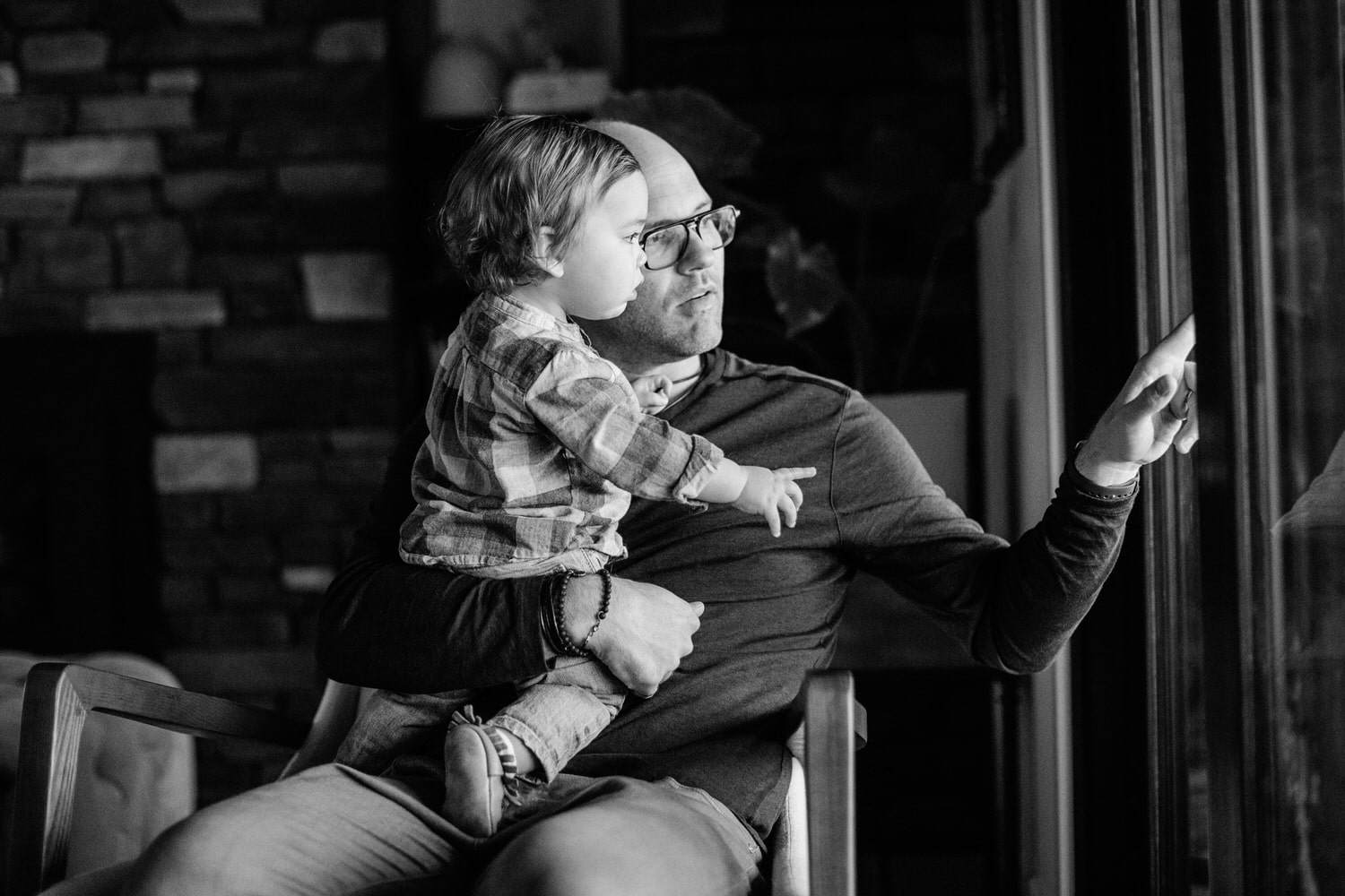 A dad holding his toddler son as they talk and look outside the window in their home