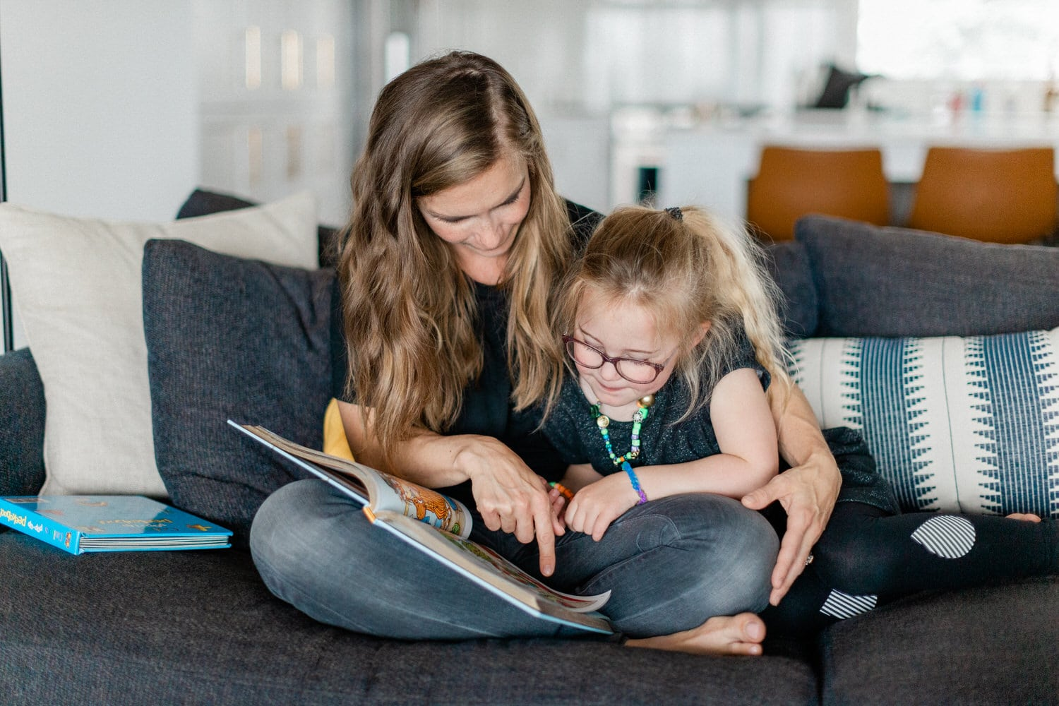 Toddler with her mom reading a book during a Calgary on location photo shoot