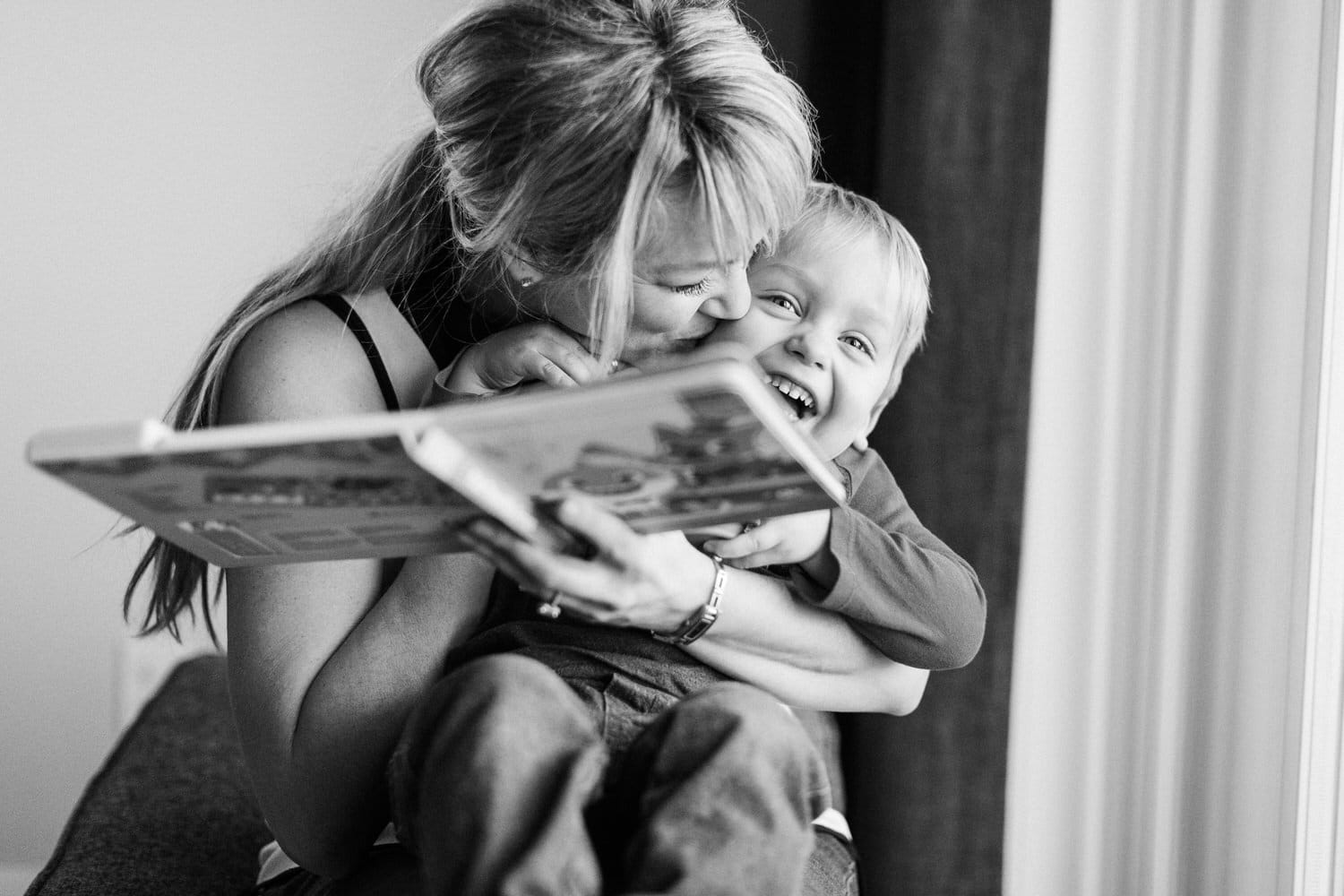 Mom and toddler playing together by a window during a Calgary based family shoot