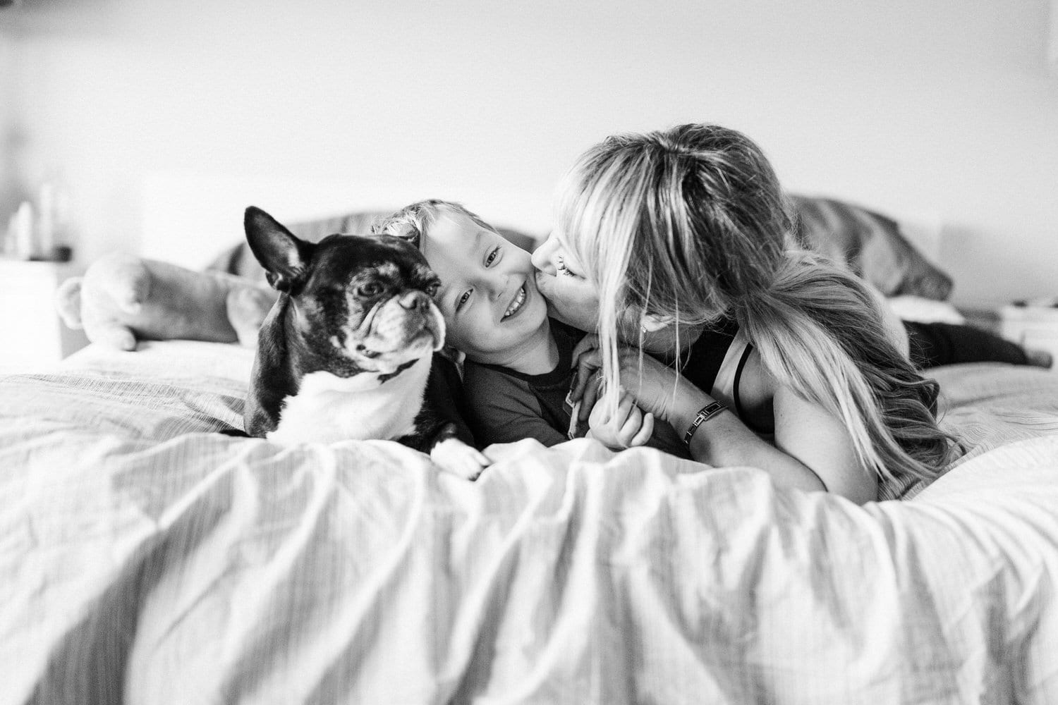 Puppy love with toddler and mom playing on their bed located in Calgary