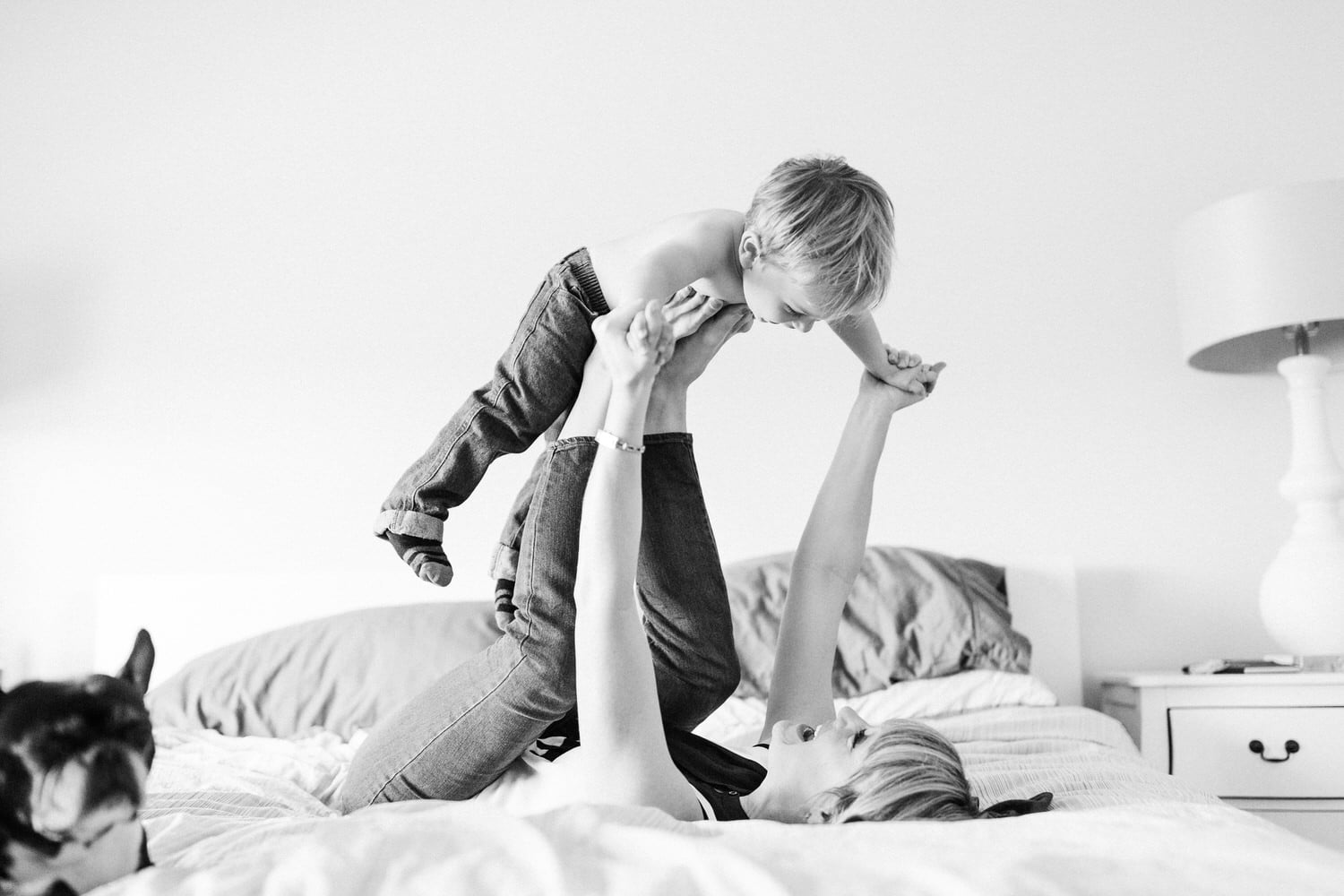 Toddler on his moms legs as they play together during a photography session in the clietns home